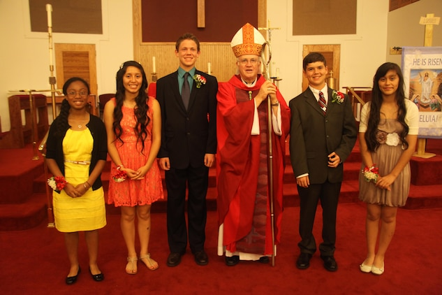 The confirmandi stand with Bishop Richard Higgins after being confirmed in the chapel aboard Marine Corps Air Station Beaufort, April 16. According to Catholic doctrine, in this sacrament they receive the Holy Spirit and become adult members of the Catholic Church.