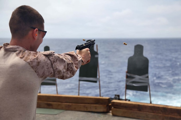 130429-M-VZ265-096 USS RUSHMORE (April 29, 2013) Sergeant Dustin Z. Gibbs, military policeman, Military Police Detachment, Combat Logistics Battalion 15, 15th Marine Expeditionary Unit, fires a M9 Pistol during a live-fire exercise on the flight deck of USS Rushmore, April 29. The servicemembers fired more than 14,000 rounds to ensure everyone was proficient with all of the battalion's weapon systems. The 15th MEU is comprised of approximately 2,400 Marines and sailors and is deployed as part of the Peleliu Amphibious Ready Group. Together, they provide a forward-deployed, flexible sea-based Marine Air Ground Task Force capable of conducting a wide variety of operations ranging from humanitarian aid to combat. Gibbs, 23, is from Oceanside, Calif. (U.S. Marine Corps photo by Cpl. Timothy Childers/Released)