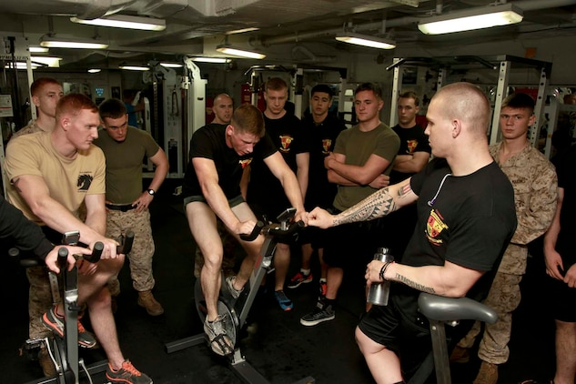USS PELELIU (April 27, 2013) Marines with Kilo Company, Battalion Landing Team 3/5, 15th Marine Expeditionary Unit, cheer on Lance Cpl. Alex P. Labier, a rifleman with 2nd Platoon, while he bikes during the Campbell Cup held in the gym of USS Peleliu, April 27. The challenge was the final competition of the Campbell Cup, a competition that brought teams from within the 15th Marine Expeditionary Unit and Peleliu Amphibious Ready Group against each other. This two-night event pitted the Command Element's team against Kilo Company's team in a showdown for the coveted Campbell Cup. The 15th MEU is deployed as part of the Peleliu Amphibious Ready Group and is comprised of approximately 2,400 Marines and sailors. Together with Amphibious Squadron Three, they provide a forward-deployed, flexible sea-based Marine Air Ground Task Force capable of conducting a wide variety of operations ranging from humanitarian aid to combat. Labier, 21, is from Ware, Mass. (U.S. Marine Corps photo by Cpl. John Robbart III/Released)