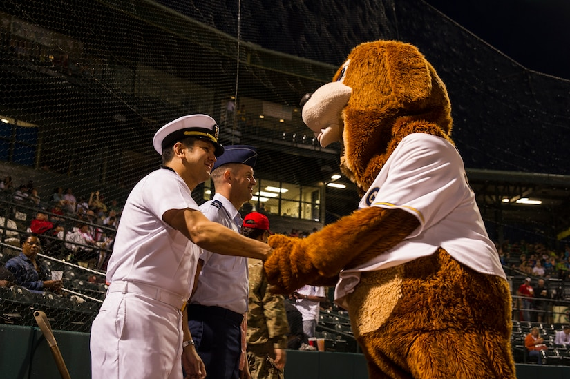 Lt. Cmdr. Victor Garza, incoming Nuclear Power Training Unit executive officer, shakes Charleston RiverDogs mascot Charlie's paw, before the first pitch during the Charleston RiverDogs Military Appreciation Night game April 25, 2013, at the Joseph P. Riley, Jr. Park in Charleston, S.C. The Charleston RiverDogs hosted Military Appreciation night to show their support for the local military. (U.S. Air Force photo/ Senior Airman George Goslin)