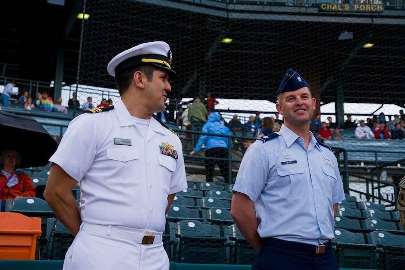 Lt. Cmdr. Victor Garza, incoming Nuclear Power Training Unit executive officer, and Lt. Col. Ryan White, 437th Aircraft Maintenance Squadron commander, wait to throw the first pitches during the Charleston RiverDogs Military Appreciation Night game April 25, 2013, at the Joseph P. Riley, Jr. Park in Charleston, S.C. The Charleston RiverDogs hosted Military Appreciation night to show their support for the local military. (U.S. Air Force photo/ Senior Airman George Goslin)
