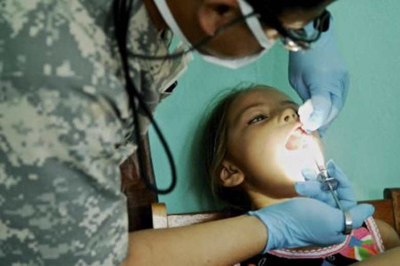 U.S. Army Capt. Blong Ly, general dentist assigned to the 352nd Combat Support Hospital, gives a young Belizean girl anesthetic at San Felipe School, Belize, April 24, 2013. Medical professionals from the U.S. and Canada provided free medical treatment during medical readiness training exercises throughout Belize as part of an on-going exercise known as New Horizons. The MEDRETES were designed to provide humanitarian assistance and medical care to people in several communities, while helping improve the skills of U.S. military medical forces. (U.S. Air Force photo by Master Sgt. James Law/Released)