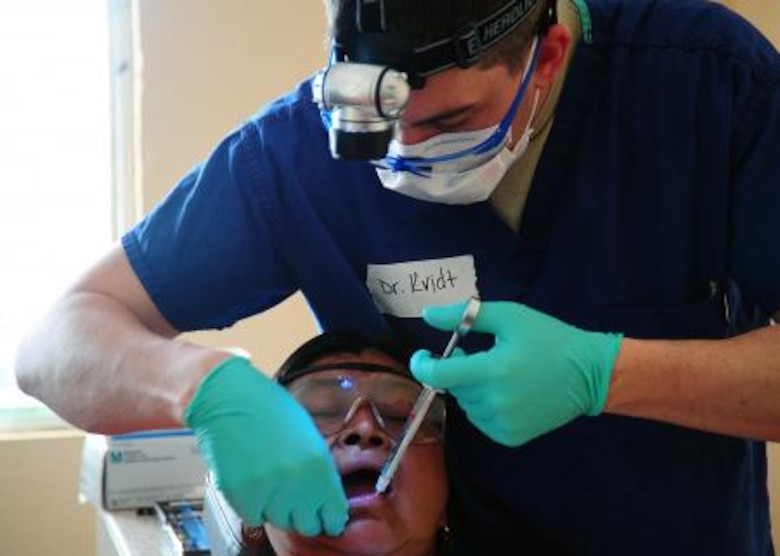 U.S. Air Force Capt. Brandon Kvidt, dental resident from Offutt Air Force Base, Neb., administers anesthesia to a Belizean woman during a dental readiness training exercise at the Punta Gorda Hospital annex in Punta Gorda, Belize, April 26, 2013. Dental professionals from the U.S. and Canada are providing free dental treatment at multiple readiness training exercises throughout Belize as part of an exercise known as New Horizons. The training exercises are designed to provide dental care to people throughout Belize, while helping improve the skills of U.S. and Canadian military medical forces. (U.S. Air Force photo by Tech Sgt. Tony Tolley/Released)