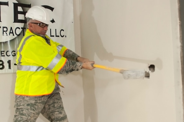 Air National Guard Chief Master Sgt. Philip Mabie, security forces manager, 140th Security Forces Squadron, takes a swing at one of the old walls in building 700 in order to kick off building renovations for what will soon be their new office space. (U.S. Air National Guard photo by Tech. Sgt. Wolfram Stumpf)