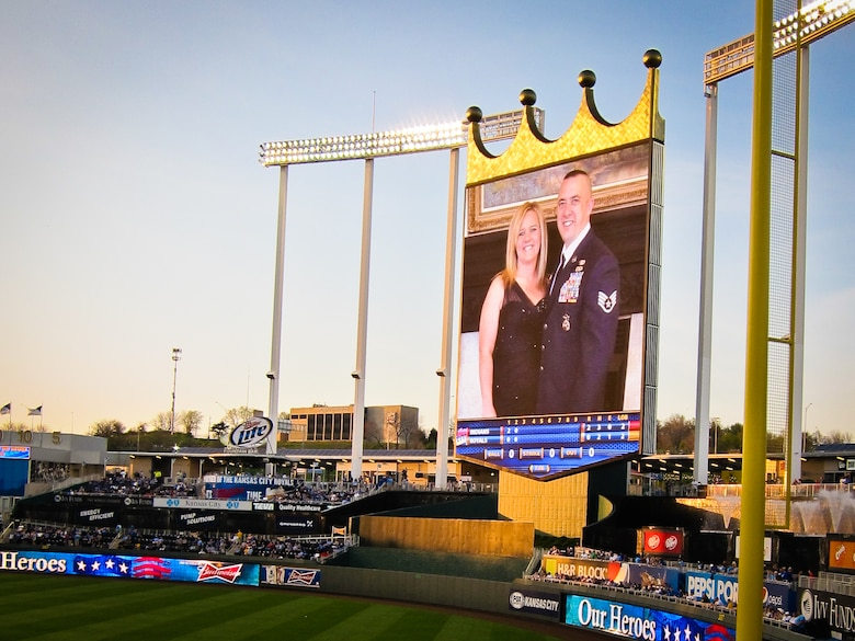 A photo of U.S. Air Force Staff Sgt. Troy Green, a squad leader with the 139th Security Forces Squadron, Missouri Air National Guard, and his wife, is displayed on a massive TV at Kauffman Stadium in Kansas City, Mo., April 28, 2013. The Kansas City Royals honored Green who received the Purple Heart for his actions while deployed to Afghanistan in 2012. (U.S. Air National Guard photo by Tech. Sgt. Michael Crane/Released)