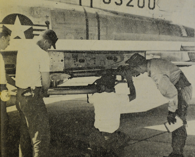 WHEELUS AB, Libya - Under 1st. Lt John Miko's (right) supervision, a weapons team load rockets on the pods of an F-100 aircraft. members of the team (left to right) are A2C Thomas Kelenske, SSgt. Gerald McKinney and SSgt. Phillip Schreier.