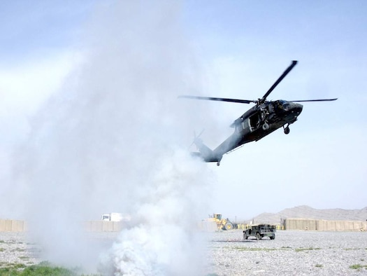 Soldiers of the 3rd Combat Aviation Brigade follow a trail of signaling smoke into a landing zone on Kandahar Airfield, Afghanistan, during a coalition-joint slingload mission. (Courtesy photo)