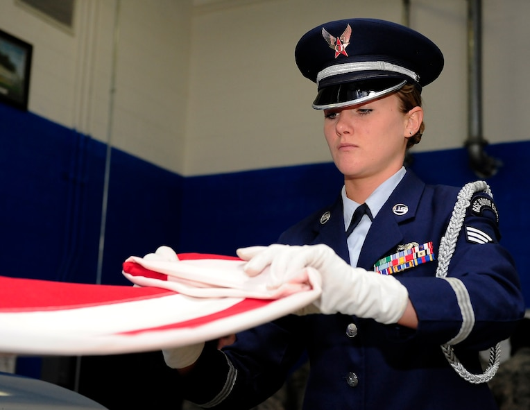 Senior Airman Julianne Pendergast, 509th Bomb Wing Honor Guard A-Team member, demonstrates a two-person flag fold at Whiteman Air Force Base, Mo., April 23, 2013. Outside of funerals, Whiteman's Honor Guard also performs at sporting events and other key base functions. (U.S. Air Force photo by Airman 1st Class Shelby R. Orozco/Released)