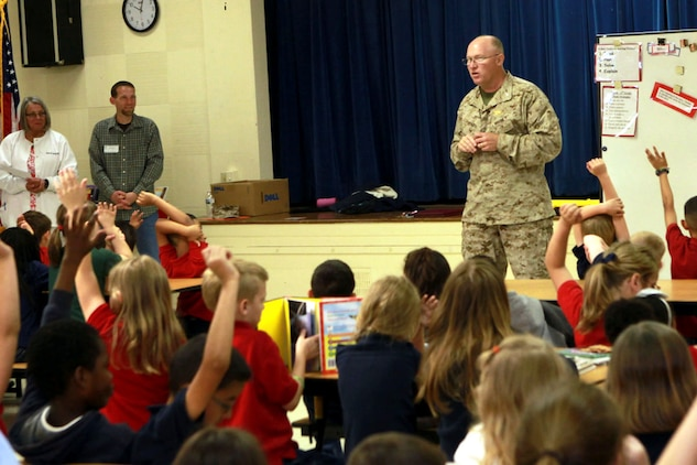 """Col. Brian Murtha asks students of Galer Elementary School what Earth Day means to them during the annual Earth Day Poster Contest at Galer Elementary, April 25. The contest aimed to teach kids more about their environment and with a theme of """"Make every day, Earth Day,"""" the top artists were rewarded with a certificate, medal and a gift card to the Marine Corps Exchange."""