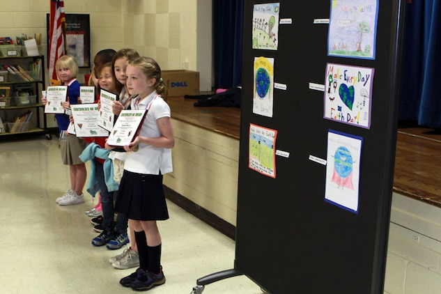 """First, second and third place winners from Galer Elementary School's annual Earth Day Poster Contest, stand in front of their award-winning posters during an awards presentation at Galer Elementary, April 25. The contest aimed to teach kids more about their environment and with a theme of """"Make every day, Earth Day,"""" the top artists were rewarded with a certificate, medal and a gift card to the Marine Corps Exchange."""