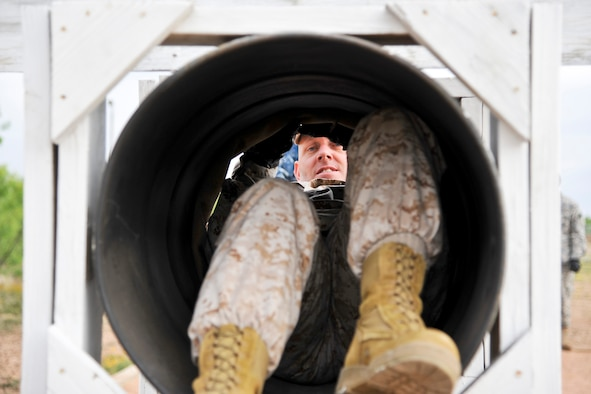 GOODFELLOW AIR FORCE BASE, Texas-- Marine Maj. Douglas March, Marine Corps Detachment Commander, climbs through a tube while participating in the Leadership Reaction Course April 30. The course is designed to help individuals discover leadership qualities and develop teamwork by completing obstacles. (U.S. Air Force photo/ Airman 1st Class Michael Smith)