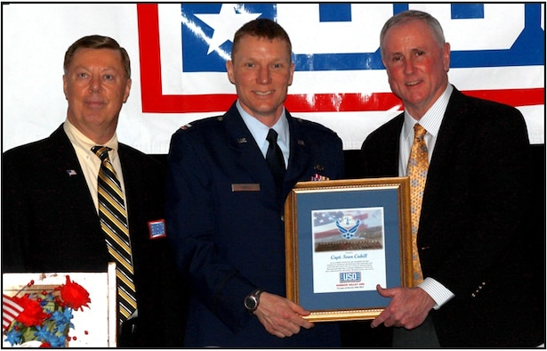 Mr. David Jubinville, the USO Board President stands with Capt. Cahill as Col. Tillman (ret)  presents the award. (Photograph by USO photographer Mr. Tom Overlock)