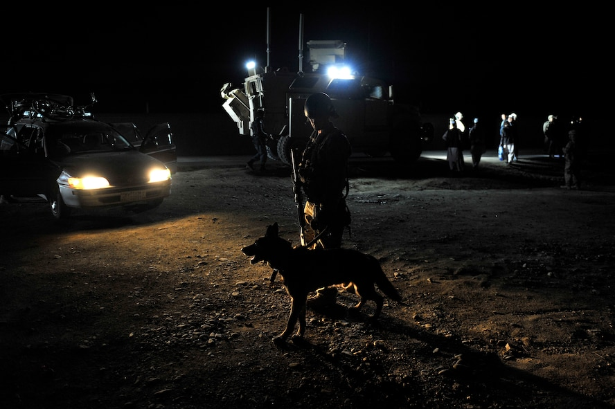 Staff Sgt. Steven Owen, 455th Expeditionary Security Forces Group Military Working Dog handler, and his dog Tex conduct a night operations search at Traffic Control Points outside of Bagram Airfield, Afghanistan, April 28, 2013. TCPs provide an unpredictable security posture in which random vehicles are selected to be swept for contraband and all occupants identified and checked.  (U.S. Air Force photo/Senior Airman Chris Willis)