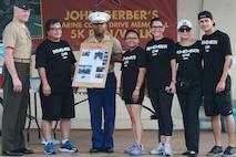 Col Scott Loch, Commanding Officer of Marine Corps Activity Guam, far left, presents a gift to the family of John Gerber and friends during the John Gerber Memorial 5 k run, commemorating health and the physical fitness of the island.