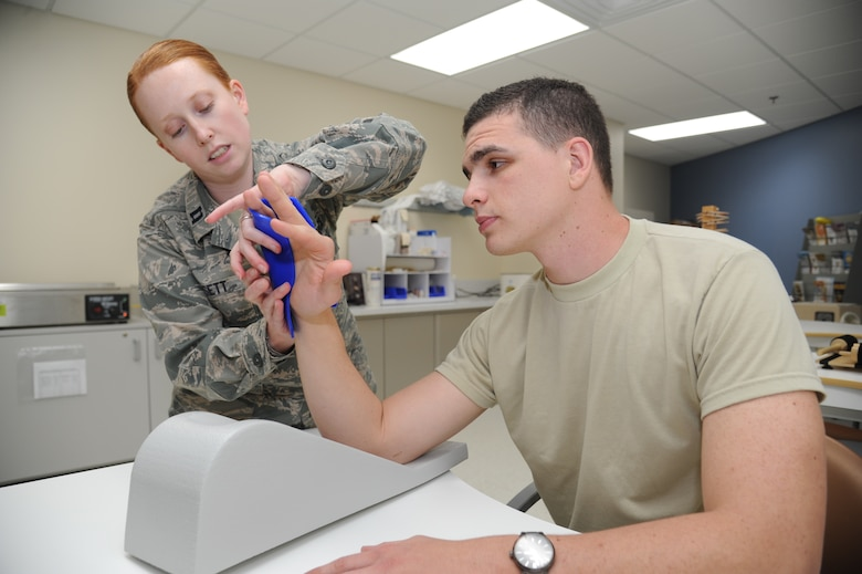 Capt. Laura Dossett, 81st Surgical Operations Squadron occupational therapist, demonstrates how to apply a fabricated splint on Airman 1st Class James Morgan, 81st MSGS, May 3, 2013, at the Keesler Medical Center, Keesler Air Force Base, Miss.  Dossett is Keesler's only occupational therapist and works primarily with arm, wrist and hand ailments that restrict every-day tasks.  (U.S. Air Force photo by Kemberly Groue)