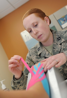Capt. Laura Dossett, 81st Surgical Operations Squadron occupational therapist, applies kinesio tape on a patient's arm for edema management May 3, 2013, at the Keesler Medical Center, Keesler Air Force Base, Miss.  Dossett is Keesler's only occupational therapist and works primarily with arm, wrist and hand ailments that restrict every-day tasks.  (U.S. Air Force photo by Kemberly Groue)