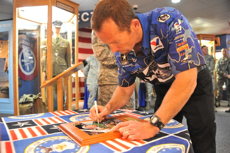 National Hot Rod Association Funny Car champion Jack Beckman signs his photo, after being added to the U.S. Air Force Enlisted Heritage Hall's Wall of Achievers May 2 at Gunter Annex. The Wall of Achievers pays tribute to former enlisted Airmen who have contributed to the growth and development of the Air Force. (U.S. Air Force photo by Staff Sgt. Sandi Percival)