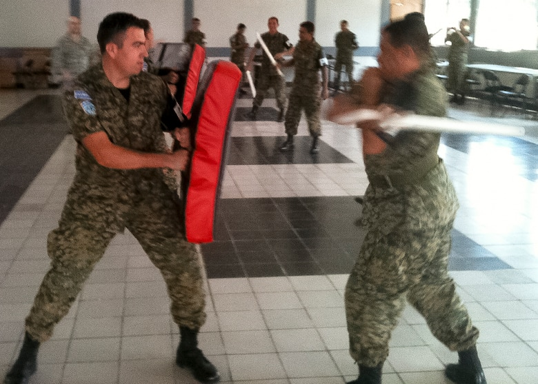 Two soldiers of the Salvadoran Army practice striking with the extendable baton as members of the 157 Security Forces Squadron look on. San Salvador, El Salvador, March 13 2013. (U.S. Air National Guard photo courtesy MSgt. Dale Snowdon)