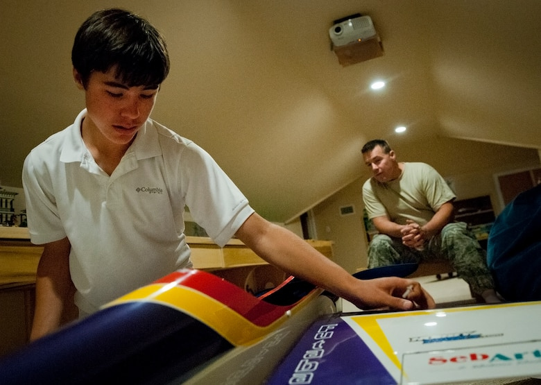 Cody Powell, the 13-year-old son of Maj. Jeff Powell, the 919th Maintenance Operations Flight commander, pieces together his competition-ready radio-controlled aircraft as his father watches in their home May 1.  Cody has won all but one of his 15 RC aircraft competitions since he and his father joined the hobby two years ago.  (U.S. Air Force photo/Tech. Sgt. Samuel King Jr.)