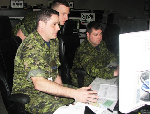 Lt. Joey Baker (left). Cpl. Adam Royer (standing) and Capt. Ben Adair of the Canadian Air Defense Sector work in the weapons section during their recent training deployment to EADS. The three were part of a group of eight Royal Canadian Air Force members from CADS that trained at EADS from March 23 through April 20.