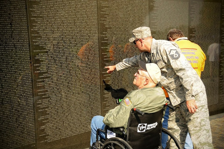 Master Sgt. Keith Holliker, an F-16 mechanic from the 180th Fighter Wing, Ohio Air National Guard, helps a Vietnam veteran look for names on the Vietnam Wall in Washington D.C., Oct. 23, 2012. This was the first Vietnam flight for the Honor Flight of Northwest Ohio.(Air National Guard photo by Master Sgt. Beth Holliker/Released).
