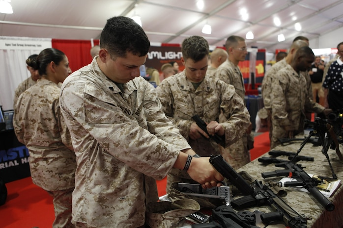 Cpl. Wally Hernandez and Cpl. Chris Davis, electronic intelligence intercept operators with 2nd Radio Battalion, handle a hand guns at a weapons display at Marine South Military Expedition aboard Marine Corps Base Camp Lejeune April 10. Marine South Military Exposition gave Marines the ability to give feedback about products they use.