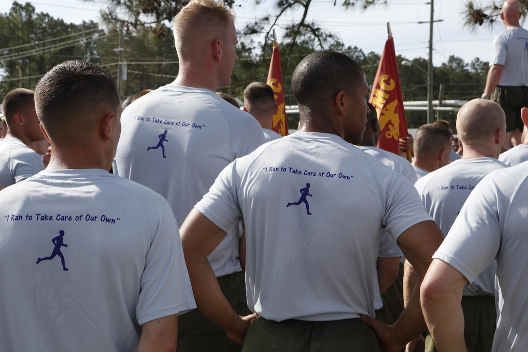 """Marines wearing T-Shirts they bought to support the Navy Marine Corps Relief Society listen to a presentation at the conclusion of a three-mile fun run April 18. The shirts feature the Navy Marine Corps Relief Society's logo on the front and the silhouette of a man running with the words """"I ran to take care of our own,"""" on the back."""