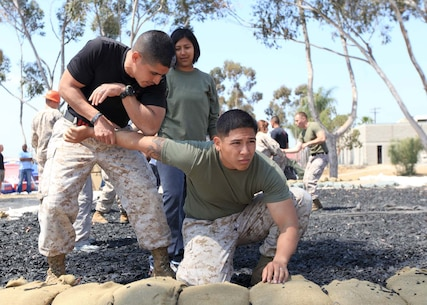 Staff Sgt. Gilberto Castillo, a Marine Corps martial arts instructor trainer and Lance Cpl. Jon Nguyen, a field wireman, with 9th Communication Battalion, demonstrates an arm bar takedown for Christina Pintos, spouse of Sgt. Alex Pintos, with 9th Comm. Bn., during a Jane Wayne Day at Camp Pendleton, Calif., May 4. Jane Wayne Day is an opportunity for Marine spouses to 'walk a mile' in the shoes of their Marines. The 9th Comm. Bn., spouses viewed equipment their Marines use day-to-day and were afforded the chance to experience some of the training they go through.