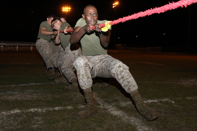 Master Sgt. Lionel Saulsberry, station postal chief, and other servicemembers with Headquarters and Headquarters Squadron, pull with all their strength during the tug of war field meet portion of an overnight field exercise at Penny Lake field here April 18, 2013. The field meet consisted of several events such as the dizzy izzy, Humvee pull and tug of war.
