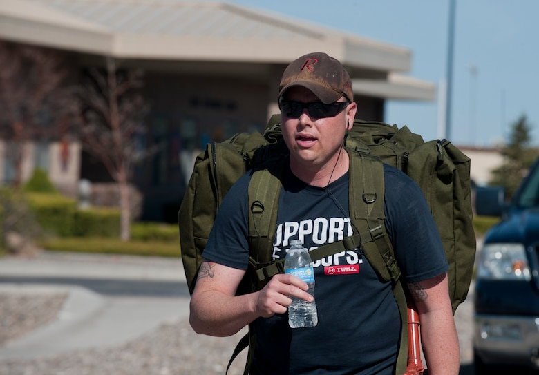 U.S. Air Force Master Sgt. Ryan Glosson, 366th Security Forces Squadron first sergeant, holds a bottle of water as he walks during his quest to become an Honorary Defender, April 26, 2013, at Mountain Home Air Force Base, Idaho. He wore a 40-pound ruck sack during a 7-mile march. (U.S. Air Force photo by Senior Airman Heather Hayward/Released)