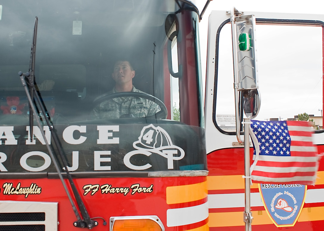"""U.S. Air Force Airman 1st Class Hunter Salge, 7th Civil Engineer Squadron, sits in the driver seat of the Remembrance Rescue Project's """"Res4cue"""" May 8, 2013, at the fire department on Dyess Air Force Base, Texas. The Remembrance Rescue Project allows Res4cue, the single remaining rescue unit from New York City in service immediately after the terror attacks, to serve as a mobile memorial to educate, honor and remember the events of Sept. 11, 2001, and all fallen firefighters throughout the country. Res4cue was parked two blocks east of the south tower when the collapse occurred. The names of firefighters who died while serving as part of Res4cue and Res3cue on 9/11, are written on the doors of the fire truck. The project stopped at Dyess while in Abilene, Texas, on a national tour visiting schools, community events and memorials, to pay tribute to the many lives lost and to always remember the events that took place on 9/11. (U.S. Air Force photo by Airman 1st Class Peter Thompson/Released)"""