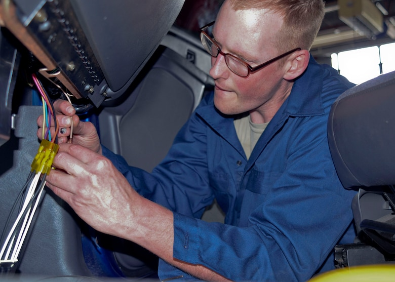 Senior Airman John Long finishes replacing a wiring component in vehicle maintenance during the unit training assembly in May 2013. (U.S. Air National Guard photo by Staff Sgt. Sean Navarro/RELEASED)