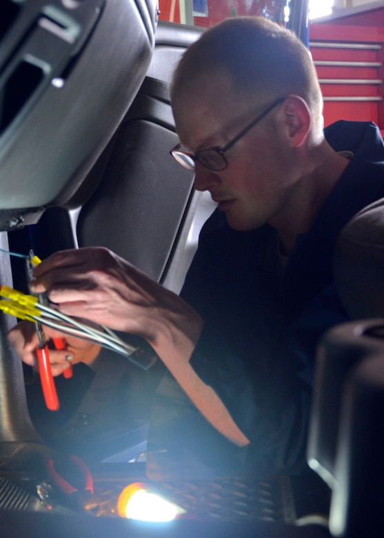 Missouri Air National Guard Senior Airman John Hall, of the 131st Logistics Readiness Squadron, replaces the wiring inside one of the 509th Bomb Wing's trucks during the unit training assembly on May 4. (U.S. Air National Guard photo by Staff Sgt. Sean Navarro/RELEASED)