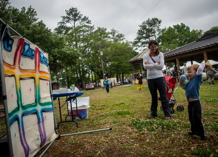 """Lindsey Beckenhauer, wife of Capt. Robert Beckenhauer, 16th Airlift Squadron C-17 Globemaster III pilot, watches her son Jake, age 3, play """"Tic-Tac-Toss"""" at the Joint Base Charleston Base Picnic May 3, 2013. The picnic was a free two-day event which included food, drinks and a live band for all Team Charleston members and their families to enjoy. (U.S. Air Force photo/ Senior Airman Dennis Sloan)"""