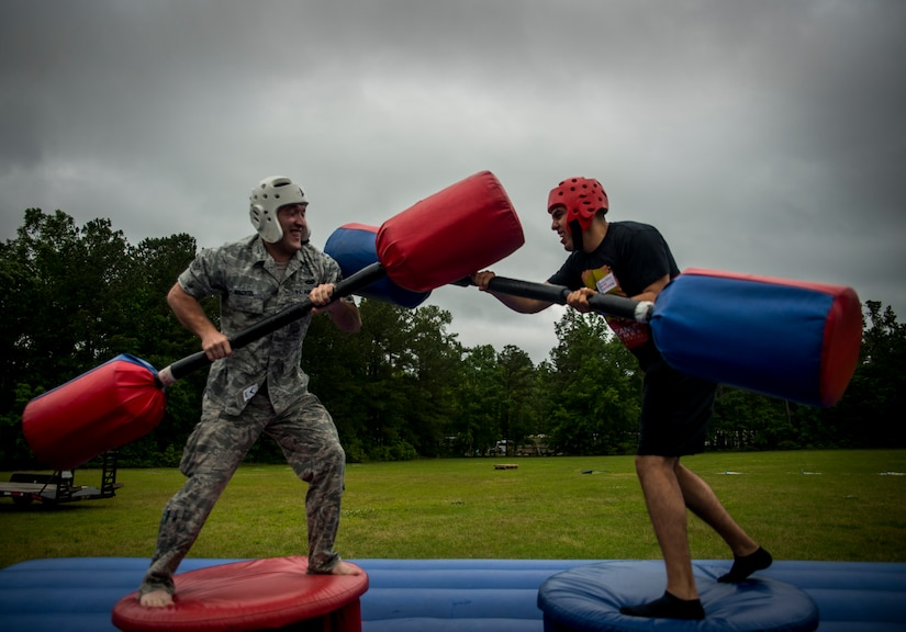 Airman 1st Class Joshua Wachtel, 628th Logistics Readiness Squadron maintenance specialist (left), tries to knock Airman 1st Class Roberto Ladino, 628th LRS maintenance specialist, off his platform during a pugil stick battle at the Joint Base Charleston Base Picnic May 3, 2013. The base picnic was a free two-day event which included food, drinks and a live band for all Team Charleston members and their families to enjoy. (U.S. Air Force photo/ Senior Airman Dennis Sloan)