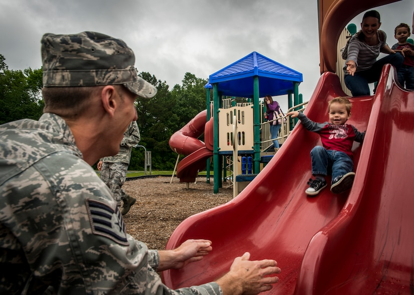 Staff Sgt. Ryan Yeager, 437th Maintenance Squadron Precision Measurement Equipment Laboratory supervisor, kneels down at the end of a slide to catch his son Levi, age 2, while his wife Danielle and Levi's twin brother Landon send Levi on his way May 3, 2013, at the Joint Base Charleston Base Picnic. The base picnic was a free two-day event which included free food, drinks and a live band for all Team Charleston members and their families to enjoy. (U.S. Air Force photo/ Senior Airman Dennis Sloan)