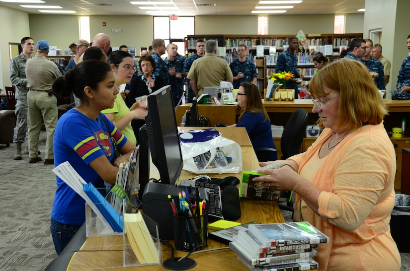 Pamela King (right),Weapons Station Branch Library technician, helps a customer May 7, 2013, at Joint Base Charleston – Weapons Station, S.C. The library recently re-opened after being closed due to renovations. (U.S. Air Force photo/Staff Sgt. Anthony Hyatt)
