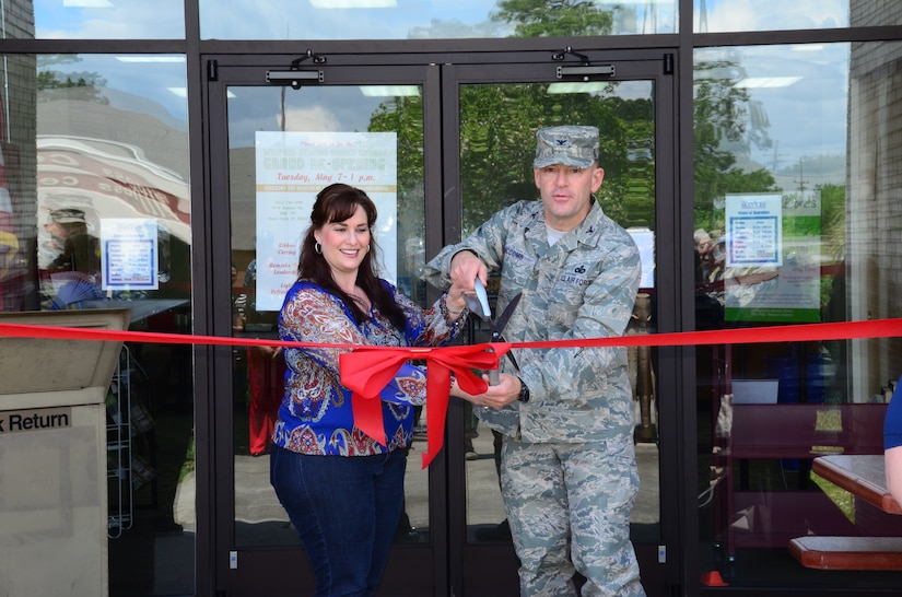 Col. Richard McComb, Joint Base Charleston commander, and Angela Aschenbrenner, JB Charleston Libraries director, cut the ribbon during the grand re-opening of the Weapons Station Branch Library May 7, 2013, at Joint Base Charleston – Weapons Station, S.C. The library re-opened after being closed for renovations in September 2012. (U.S. Air Force photo/Staff Sgt. Anthony Hyatt)