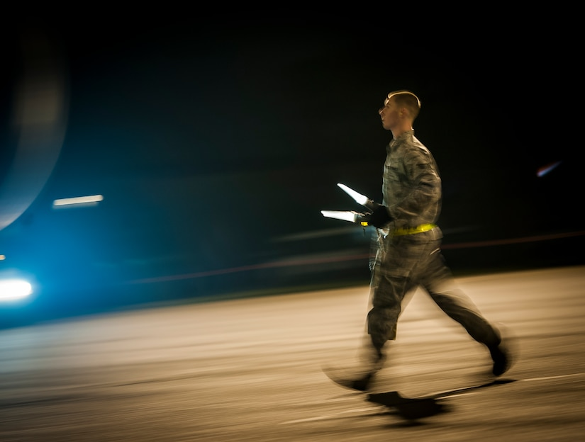 An Airman with the 437th Aircraft Maintenance Squadron guides a staircase truck into place for the Airmen from the 15th Airlift Squadron to deplane the aircraft which returned them to Joint Base Charleston – Air Base, May 4, 2013, after a two-month deployment to Southwest Asia. The squadron flew 1,000 sorties while safely moving 40 million pounds of cargo and 5,000 passengers throughout the area of responsibility. The squadron also precisely executed 33 combat airdrops resupplying forward operating bases throughout Southwest Asia with 900 bundles of supplies. (U.S. Air Force photo/ Senior Airman Dennis Sloan)