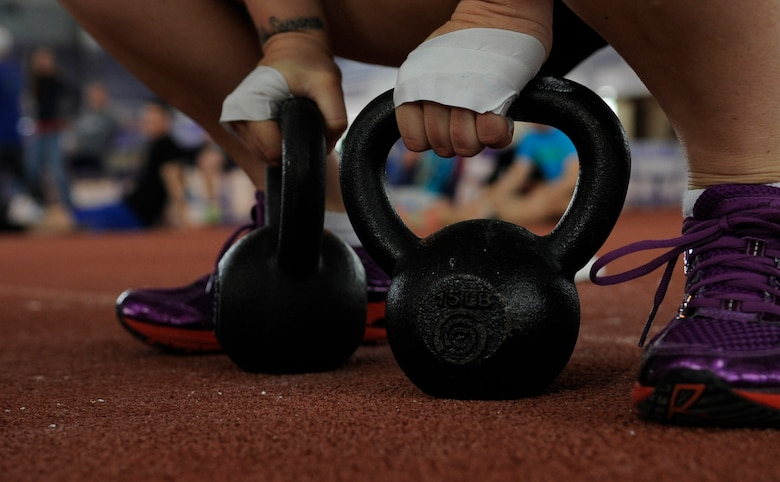 Staff Sgt. Samantha Scott, 509th Bomb Wing Command Post training manager, prepares to use kettle bells during the last event at the K-State CrossFit Challenge in Manhattan, Kan., April 27, 2013.  The event consisted of kettle bell squat clean thrusters, box jumping, an 800-meter run and deadlifts. (U.S. Air Force photo by Staff Sgt. Alexandra M. Boutte/Released)