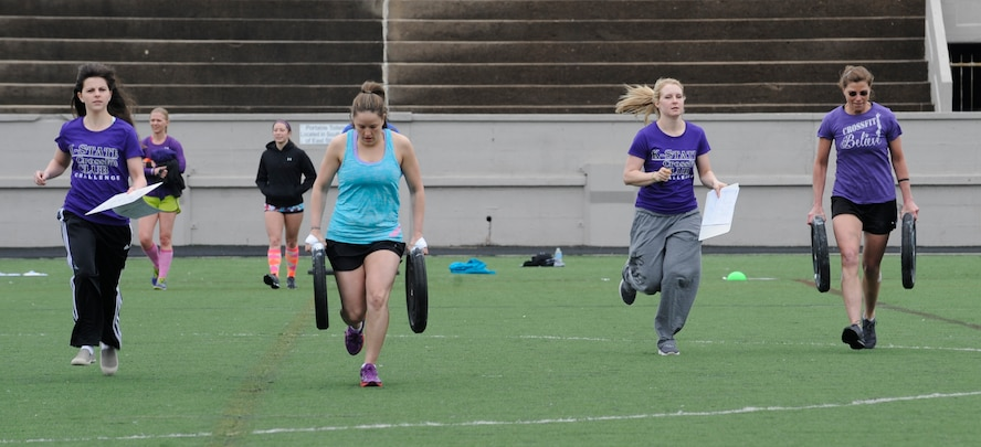 Staff Sgt. Samantha Scott, 509th Bomb Wing Command Post training manager, and her teammate race with 25-pound plates across a football field during the K-State CrossFit Challenge in Manhattan, Kan., April 27, 2013.  After dropping the weights, the participants ran the bleachers eight times, doing burpees between each set. (U.S. Air Force photo by Staff Sgt. Alexandra M. Boutte/Released)