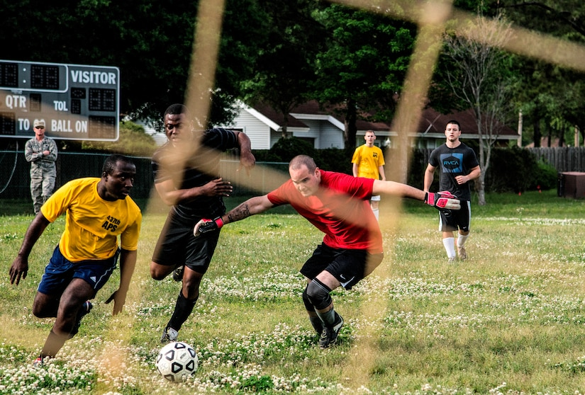 Senior Airman Michael Oheone (middle), 628th Logistics Readiness Squadron intramural soccer team player, attempts to get past Staff Sgt. Theophilus Okrah (left) and Senior Airman Ernest Love (right), 437th Aerial Port Squadron intramural soccer team defenders May 2, 2013, at Joint Base Charleston – Air Base, S.C.. The 628th LRS soccer team defeated the 437th APS soccer team 8 – 2 Joint Base Charleston's 2013 intramural soccer championship game. (U.S. Air force photo/Staff Sgt. Rasheen Douglas)