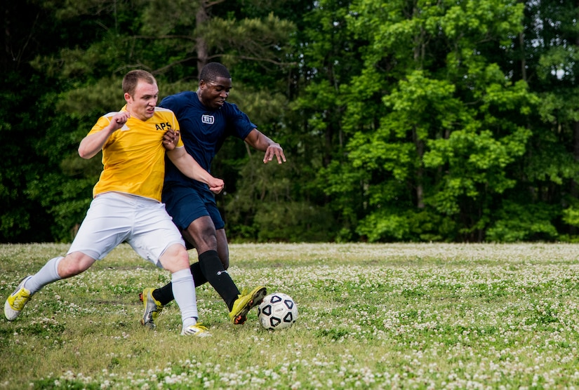 Airman 1st Class Kelvin Zelee (right), 628th Logistics Readiness Squadron intramural soccer team player, attempts to dribble past Senior Airman Jesse Ritz, 437th Aerial Port Squadron intramural soccer team defender May 2, 2013, at Joint Base Charleston – Air Base, S.C. The 628th LRS soccer team defeated the 437th APS soccer  team 8 – 2 in Joint Base Charleston's 2013 intramural soccer championship game. (U.S. Air force photo/Staff Sgt. Rasheen Douglas)