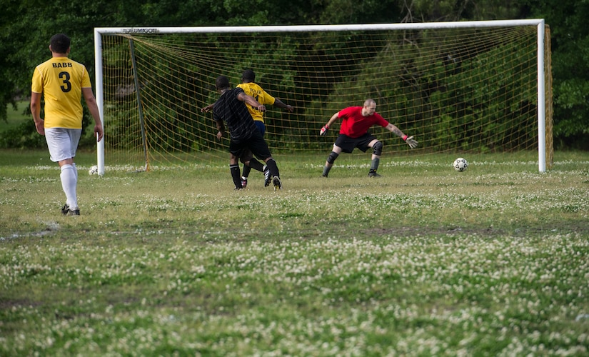 628th Logistics Readiness Squadron intramural soccer team scores a goal against Senior Airman Ernest Love, 437th Aerial Port Squadron intramural soccer team goalie May 2, 2013, at Joint Base Charleston – Air Base, S.C. The 628th LRS soccer team defeated the 437th APS soccer team 8 – 2 in Joint Base Charleston's 2013 intramural soccer championship game. (U.S. Air force photo/Staff Sgt. Rasheen Douglas)