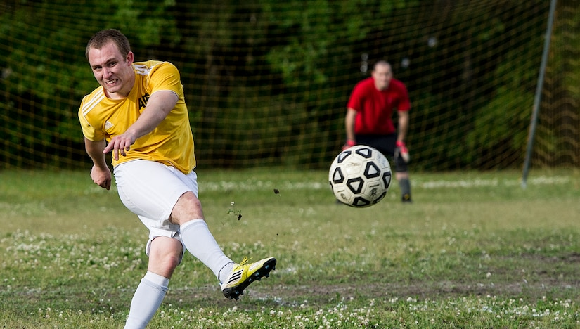 Senior Airman Jesse Ritz, 437th Aerial Port Squadron intramural soccer team player, dribbles past Master Sgt. Andred Jackson, 628th Logistics Readiness Squadron intramural soccer team defender May 2, 2013, at Joint Base Charleston – Air Base, S.C. The 628th LRS soccer team defeated the 437th APS soccer team 8 – 2 in Joint Base Charleston's 2013 intramural soccer championship game. (U.S. Air force photo/Staff Sgt. Rasheen Douglas)