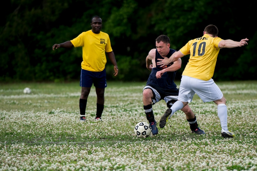 Capt. Kent Germaine (black shirt), 628th Logistics Readiness Squadron intramural soccer team player, dribbles past Senior Airman Jesse Ritz, 437th Aerial Port Squadron intramural soccer team defender May 2, 2013, at Joint Base Charleston – Air Base, S.C.. The 628th LRS soccer team defeated the 437th APS soccer team 8 – 2 win in Joint Base Charleston's 2013 intramural soccer championship game. (U.S. Air Force photo/Staff Sgt. Rasheen Douglas)