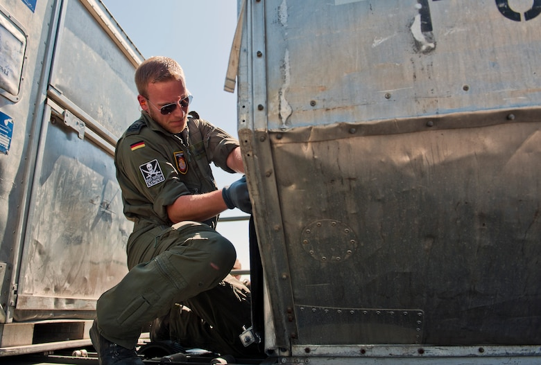 A German service member straps down cargo onto a Tunner 60K loader May 1, 2013, at Incirlik Air Base, Turkey. The German soldiers were switching out with other soldiers to support NATOs commitment to Turkey's solidarity. They were aided by the 728th Air Mobility Squadron while loading and unloading cargo. (U.S Air Force photo by Senior Airman Daniel Phelps/Released)