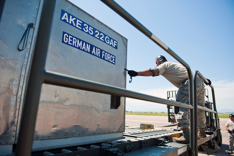 Staff Sgt. Teve Molioo, 728th Air Mobility Squadron air freight supervisor, adjusts cargo on a Tunner 60K loader for the German army as Tech. Sgt. Christopher Dungca, 728th AMS air freight NCO in charge, ensures everything is in line May 1, 2013, at Incirlik Air Base, Turkey. The 728th AMS provides around-the-clock support for U.S. and NATO forces. (U.S. Air Force photo by Senior Airman Daniel Phelps/Released)