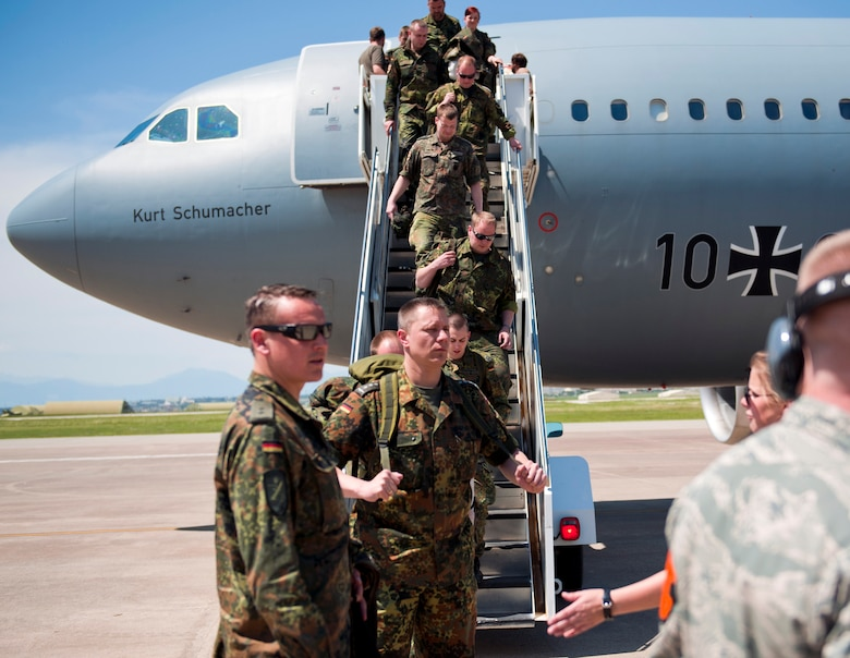 Airman 1st Class Trevor Caldwell, 728th Air Mobility Squadron air freight journeyman, directs German soldiers to the 728th AMS passenger terminal May 1, 2013, at Incirlik Air Base, Turkey. German personnel arrived at Incirlik as part of their deployment turnover to support the NATO mission of deterrence of hostile actions along the Turkish-Syrian border. (U.S. Air Force photo by Senior Airman Daniel Phelps/Released)