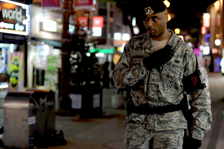 Staff Sgt. Damian Anderson, 51st Security Forces Squadron town patrolman, listens to his radio communication system during a patrol of the Songtan Entertainment District outside of Osan Air Base, Republic of Korea, May 4, 2013. The town patrol team's primary mission is force protection and handling any off base law enforcement issues involving Department of Defense personnel. Each patrol team consists of at least two 51st SFS members and a KATUSA, or Korean Augmentee to the U.S. Army member. (U.S. Air Force photo/Staff Sgt. Sara Csurilla)